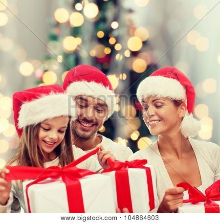 family, christmas, generation, holidays and people concept - happy family in santa helper hats with gift boxes sitting over christmas tree lights background