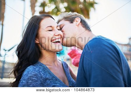 boyfriend giving surprise kiss to girlfriend shot with selective focus poster