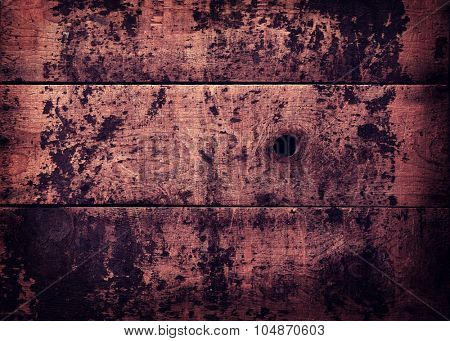 Grungy, weathered and burnt / charred wooden wall with an knot hole.Intentionally shot with retro-vintage color.