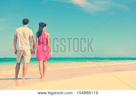 Couple standing on beach travel holding hands. Rear view of multiethnic romantic couple on shore. Young partners are watching sea. Tourists are enjoying their summer vacation at beach. poster