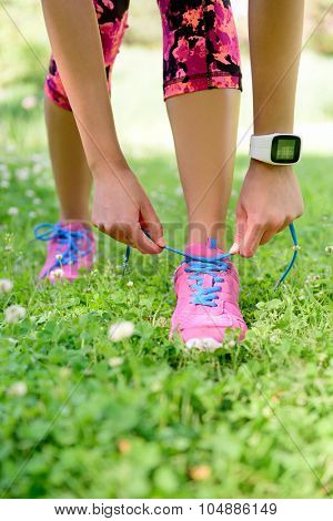 Weight loss - runner tying laces wearing smartwatch heat rate monitor and activity tracker for cardio exercise. Woman getting ready for jogging workout. Closeup of running shoes.