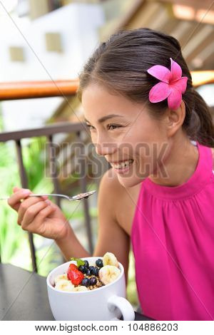 Acai bowl - girl eating healthy food outdoors. Woman enjoying acai bowls made from acai berries and fruits outdoors for breakfast.