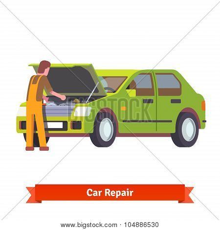 Car mechanic checking engine at car service