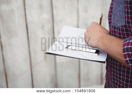 Cropped image of man with smartphone writing on book against wooden wall