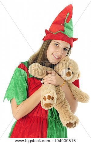 A pretty teen elf looking at the viewer as she happily hugs a tan teddy bear ready for Christmas giving.  On a white background.