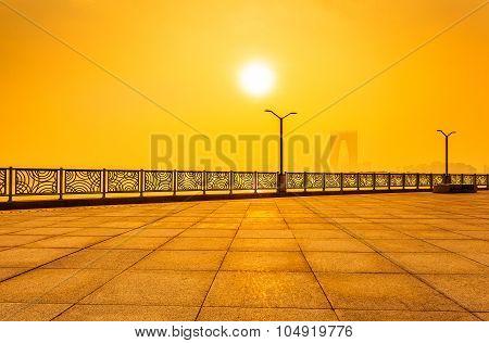 empty pedestrian walkway against sunlight,orange toned .