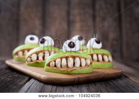 Scary halloween edible apple monsters healthy natural dessert. Horror party decoration delicious sna