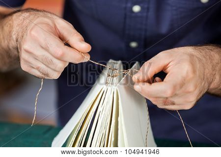 Midsection of male worker binding pages in paper factory