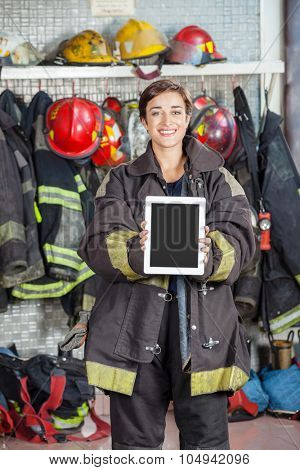 Portrait of confident firewoman showing digital tablet with blank screen at fire station
