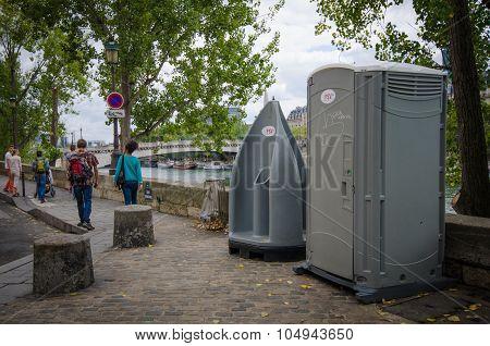 People walk by public toilet facilities on Quai d'Orleans