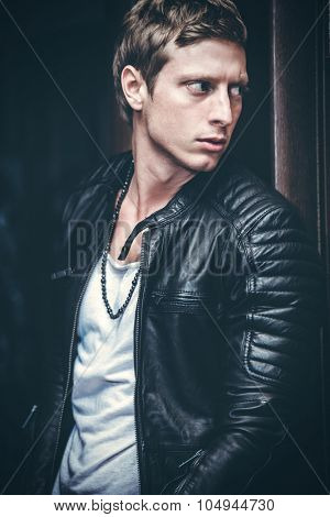 handsome young man in leather jacket and white t-shirt indoor shot in doorpost