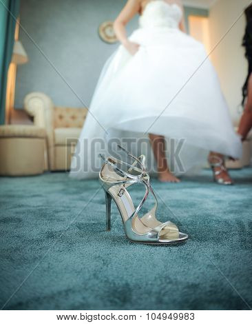 Wedding silver shoe closeup with a bride in background. High heels bridal shoe on carpet