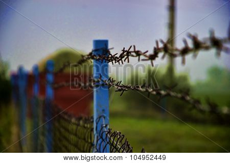Close Up Of A Rusty Metallic Barbed Wire Fence.