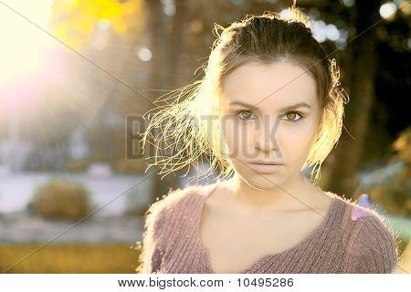 A Beautiful Brunette Stands In The Autumn Sun Light