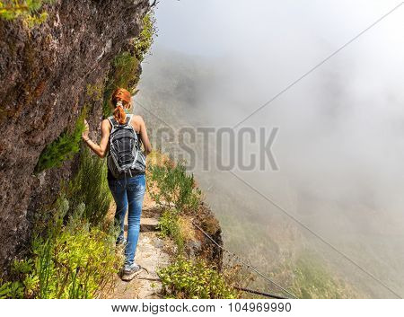 Young woman walking in the path on the mountain edge, Portugal, Madeira
