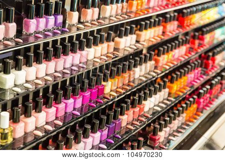 Set of different nail varnishes on shelves in cosmetic store