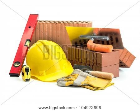 Perforated bricks, stainless steel trowel, yellow helmet, protective gloves and spirit level isolated on white