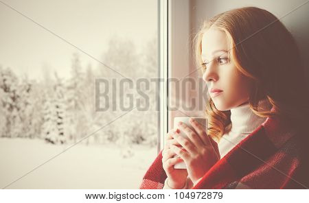 Pensive Sad Girl With A Warming Drink Looking Out The Window In The Winter Forest