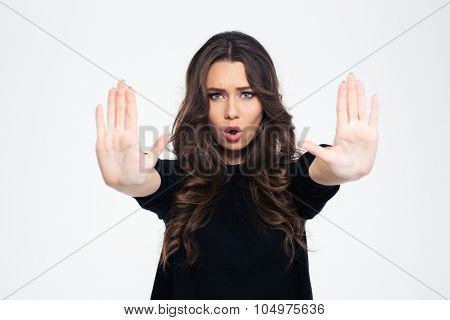 Portrait of a beautiful girl showing stop sign with palms isolated on a white background
