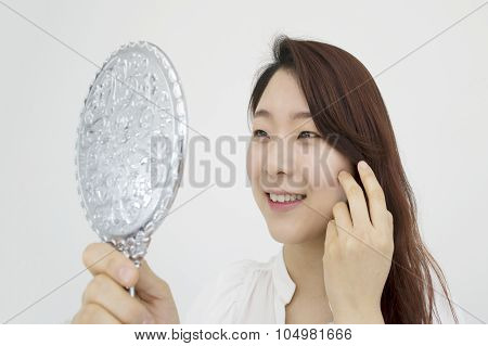 Pretty woman looking at herself in the mirror