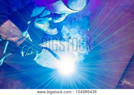Heavy industry welder worker in protective mask hand holding arc welding torch working on metal construction poster