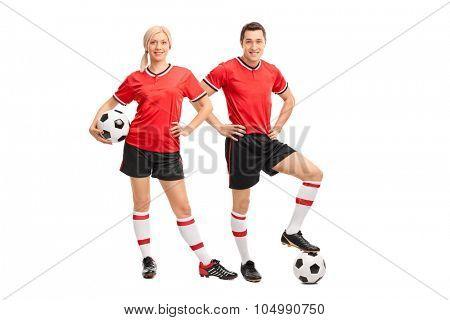 Full length portrait of a male and female football players in red jerseys looking at the camera isolated on white background