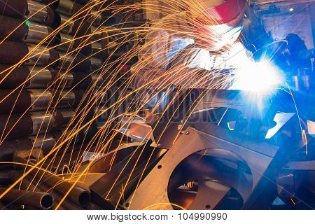 sparks while welder uses torch to welding poster
