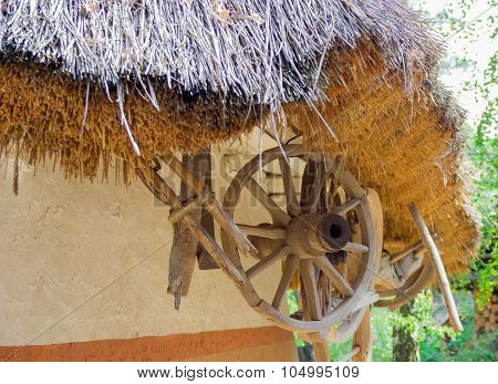 Fragment Of An Old Thatched Roof And Under It The Wooden Wheel