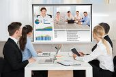 Group Of Businesspeople Attending Video Conference In Office poster