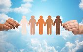 community, unity, population, race and humanity concept - multiracial couple hands holding chain of paper people pictogram over blue sky and clouds background poster