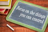 Focus on the things you can control - advice on the slate blackboard with a white chalk and a stack of books against rustic wooden table poster