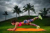 Slim fitness young woman Athlete girl doing plank exercise outside. Concept training workout crossfit gymnastics cross fit. poster