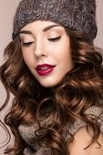 Beautiful girl with a gentle make-up, curls  in winter brown knit cap. Warm winter image. Beauty face. Picture taken in the studio. poster