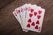 flush royal combination cards lying on a wooden table poster