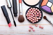 Makeup cosmetics products on white wooden background with copy space. Cosmetics make up artist objects: lipstick, eye shadows, eyeliner, concealer, powder, tools for make-up. Selective focus poster