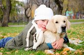 Boy playing in autumn park with a golden retriever. poster