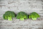 Fresh raw organic broccoli on a wooden background top view poster