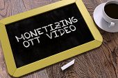 Monetizing OTT Video Handwritten on Yellow Chalkboard. Business Concept. Composition with Chalkboard and Cup of Coffee. Top View Image. poster