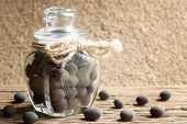 dialium cochinchinensis or velvet tamarind fruit in glass bottle on wood table poster