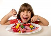 cute European female child smiling happy eating candy like crazy with fork and knife in sugar abuse unhealthy sweet nutrition concept children candy addiction and kids dental care poster