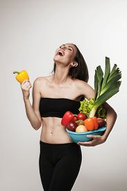 Portrait Of Young Fit Woman Holding Vegetables