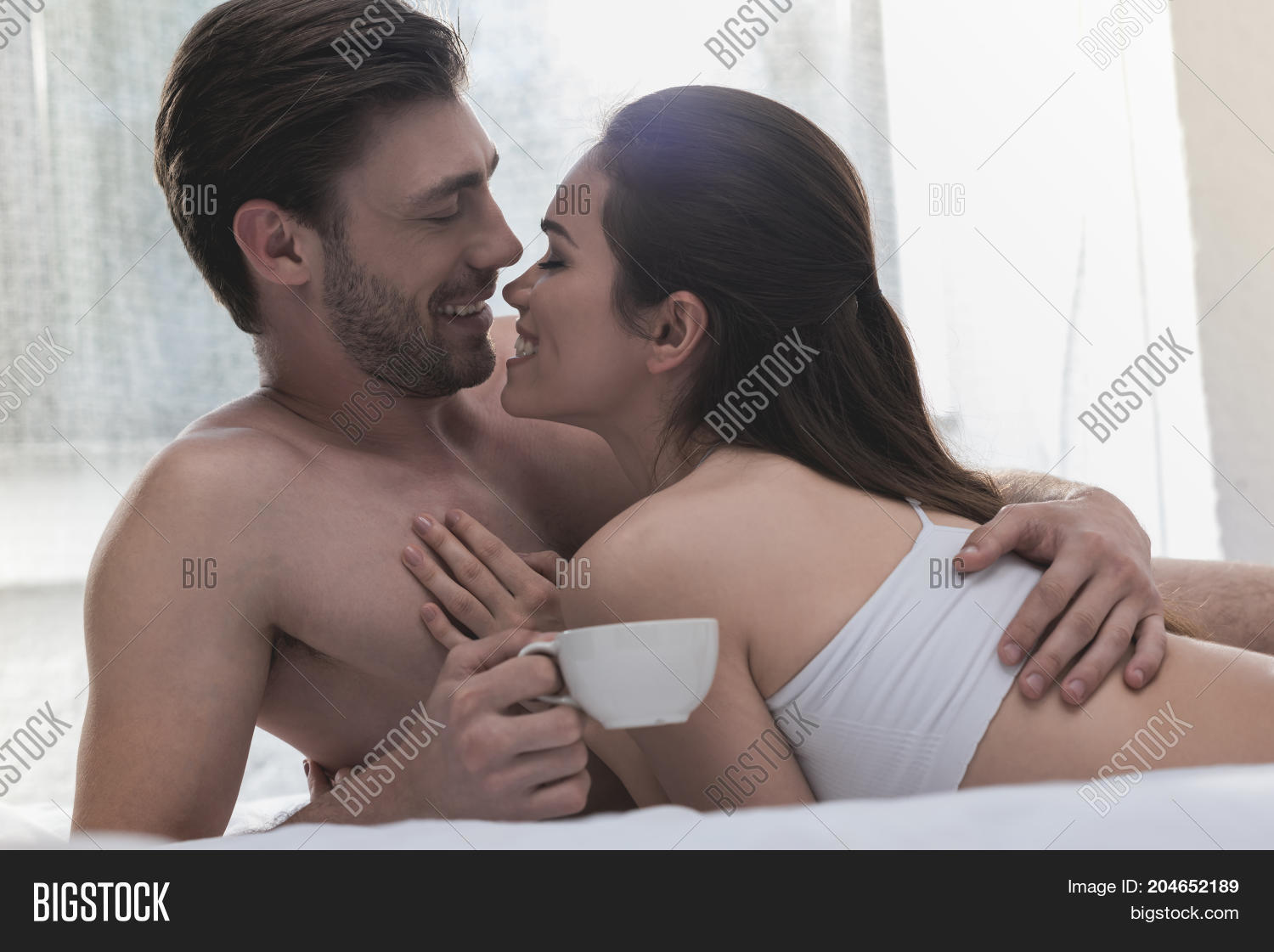 Couple Cuddling In Bed At Morning