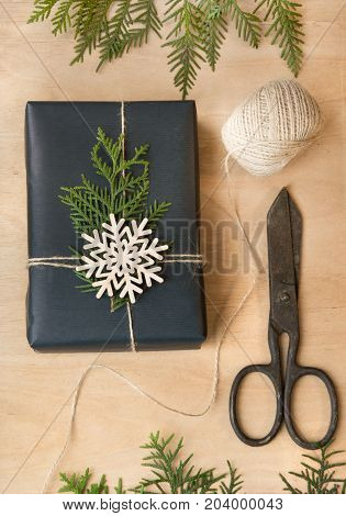 Christmas gift box wrapped in black paper with snowflakes around branch cypress on wooden surface. Top view.
