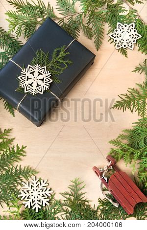 Christmas gift box wrapped in black paper with snowflakes and branch cypress around on wooden surface.