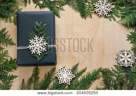 Christmas gift box wrapped in black paper with snowflakes and branch cypress around on wooden surface. Copy space.
