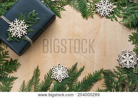 Christmas gift box wrapped in black paper with snowflakes and branch cypress around on wooden surface.Copy space.