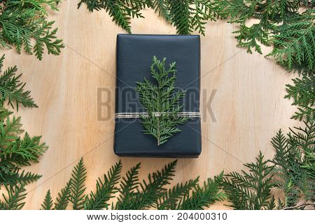 Christmas gift box wrapped in black paper with decor of branch cypress on wooden surface.