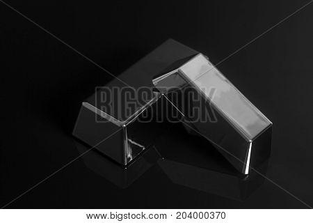 Silver bullion on a black background .