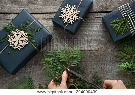 Preparation for Christmas. Workshop of decoration gift box from twine branch and snowflakes. Woman prepare a present. Top view and copy space. Flat lay. Workshop.