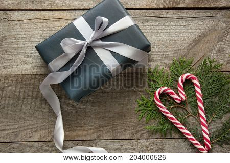 Christmas gift box wrapped in black paper with candy cane around branch cypress on wooden surface.